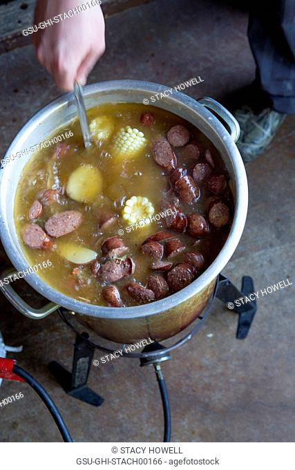 Person Cooking Low Country Boil with Corn and Sausages