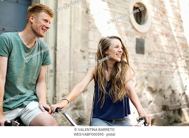 Couple with bicycles in front of an old church watching something