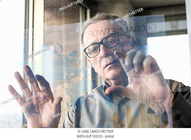Senior businessman touching transparant projection screen in office