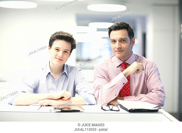 Businessman and teenage boy in office
