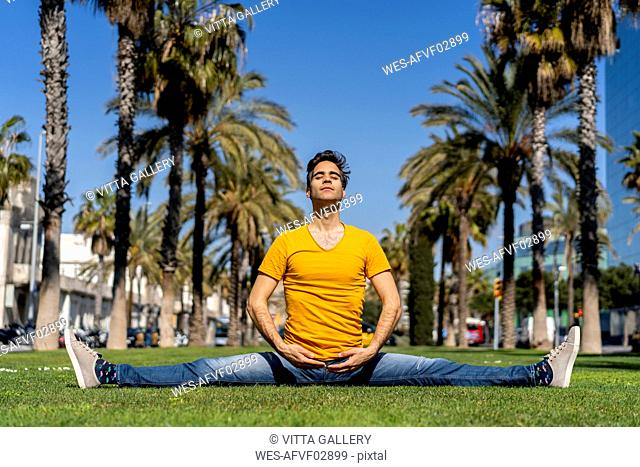 Spain, Barcelona, man practicing yoga on lawn in the city