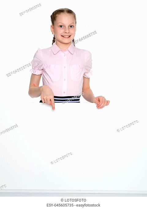 A beautiful little girl points a finger at an empty white banner in which you can insert text with your company's advertisement