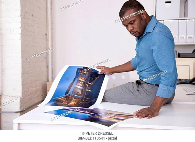 Black businessman looking at photographs in office