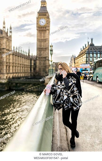 UK, London, young woman talking on phone on Westminster Bridge