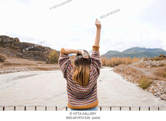 Spain, rear view of happy young woman in Ordesa National Park