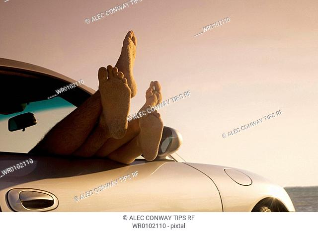 Feet sticking out of a car window