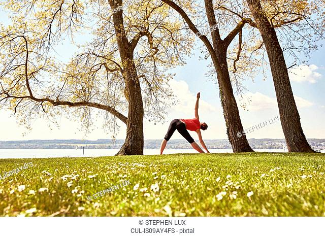 Rear view of woman, in yoga position by lake