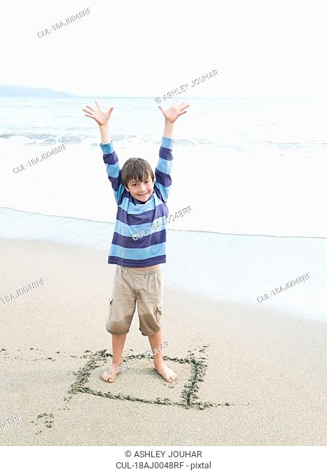 Boy standing in square drawn in sand