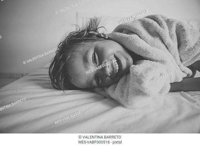 Portrait of laughing little boy with shower towel lying on the bed after taking a bath