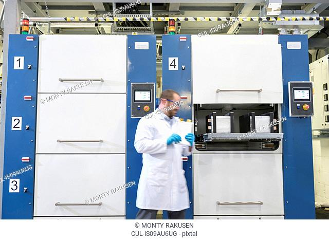 Scientist with lithium ion pouch cell manufacture machine in battery research facility