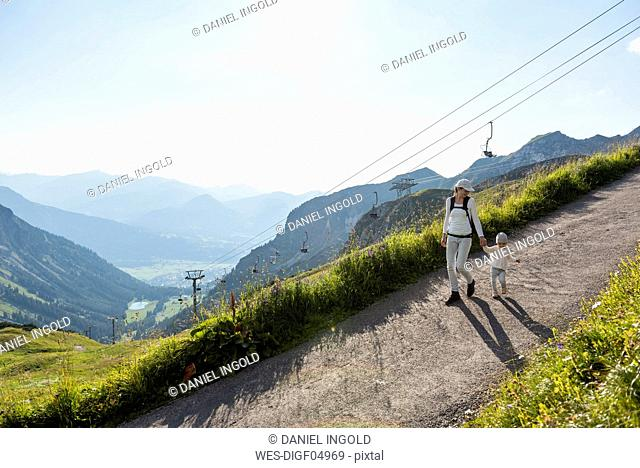 Germany, Bavaria, Oberstdorf, mother and little daughter on a hiking trip in the mountains
