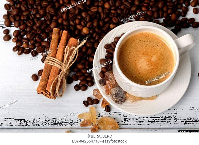 A cup of coffee with fried coffee beans, cinnamon and sugar candy. on white wooden background