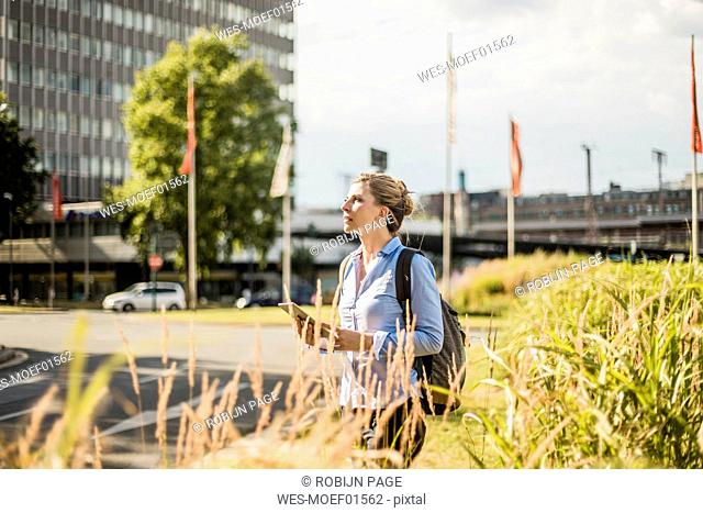 Woman with backpack and tablet in the city