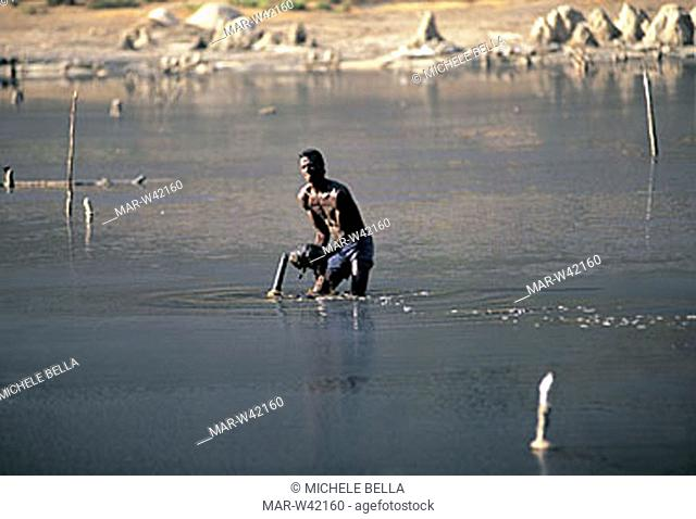 man into the salted lake in the crater, el sod, ethiopia