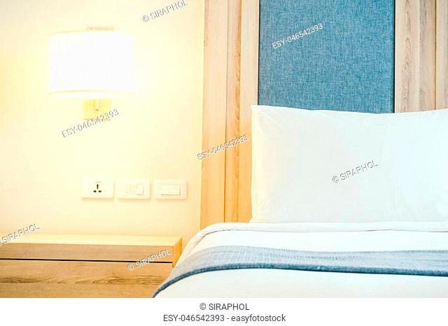 White pillow on bed with light lamp decoration interior of bedroom - Vintage soft filter