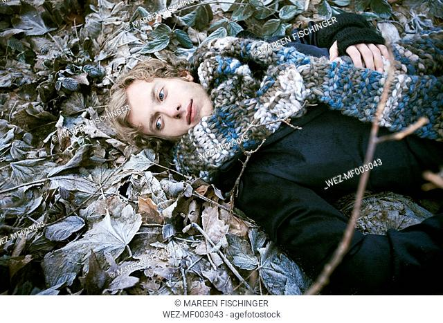Young man dressed with a thick scarf laying down between icy leaves