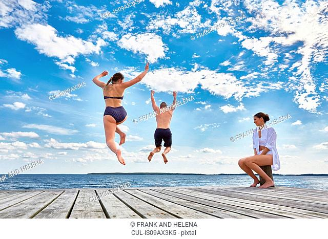 Young woman sitting on post on wooden pier, watching friends jump into sea, rear view