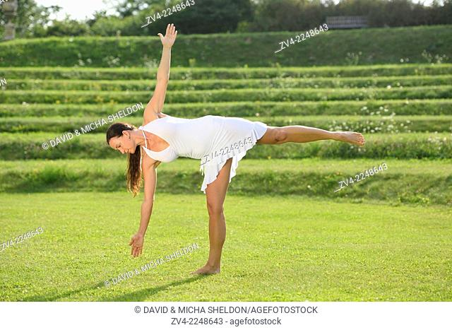 Middle aged woman doing yoga in a park in summer, Germany