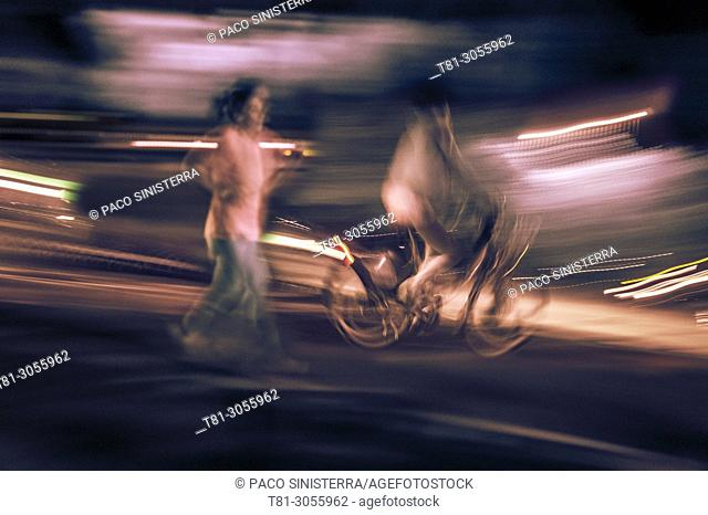 Night shot of girl running and boy on bicycle, Castellon, Spain