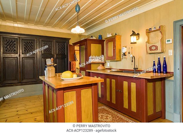Ocre and burgundy coloured cherrywood island and cabinets plus brown wooden armoire for storing pies in kitchen inside an old circa 1805 Canadiana cottage style...
