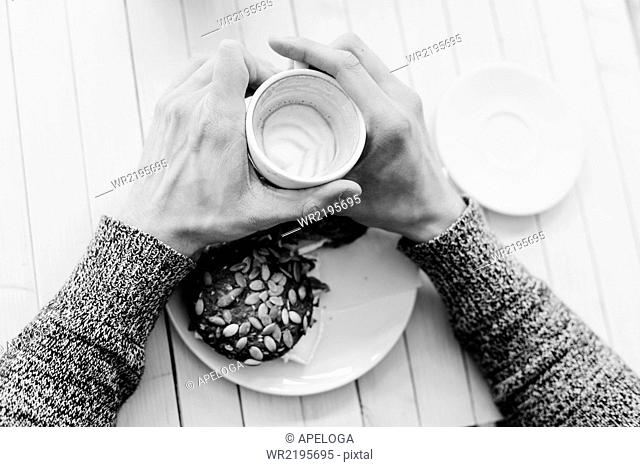 High angle view of man's hands holding coffee cup at cafe table