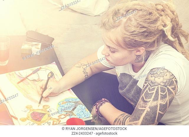Candid photo of a beautiful blonde girl in early twenties drawing up a complex water colour sketch on padded paper. Graphic designer