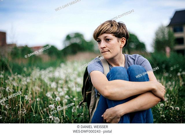 Portrait of young woman sitting on a meadow hugging knees