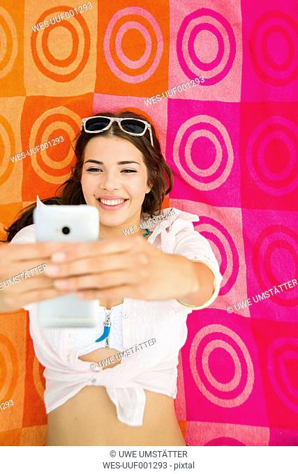 Portrait of smiling young woman lying on beach towel taking a selfie