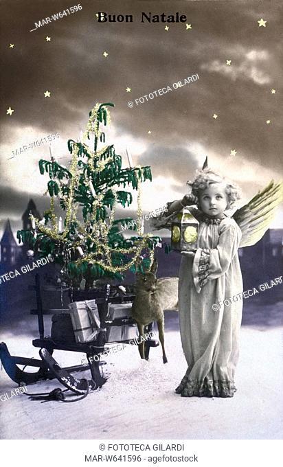 NATALE piccolo angelo bambino accanto alla slitta di Babbo Natale carica di doni: con una lanterna illumina i passi del grande vecchio