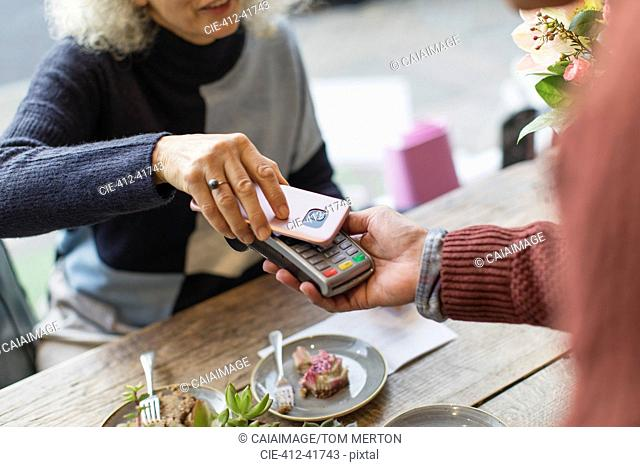 Woman with smart phone using contactless payment at cafe