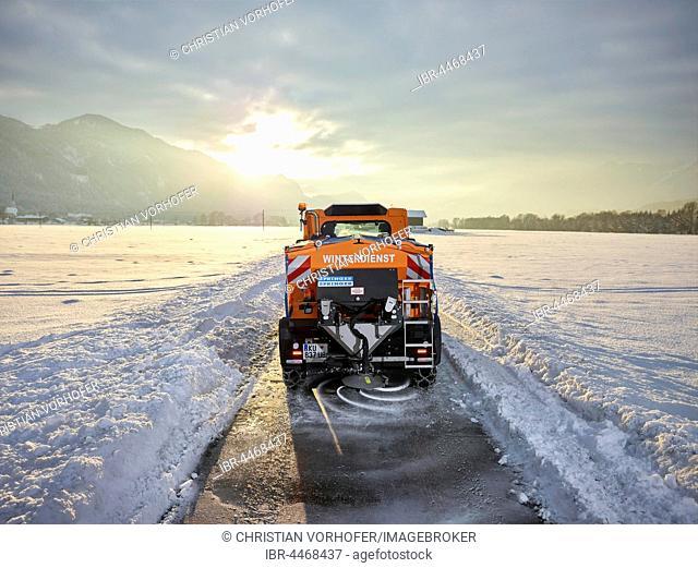 Snow plow dispenses salt on road, winter maintenance, Inntal, Tyrol, Austria