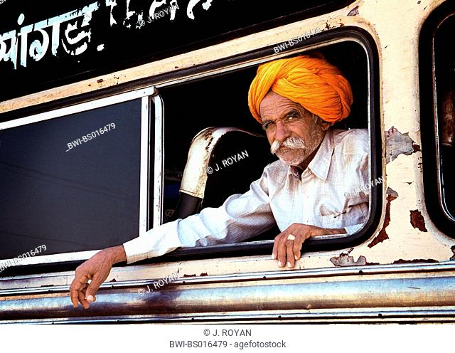man with orange turban looking out an old bus, India