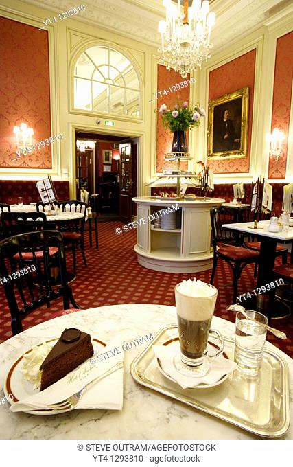 A slice of Original Sacher- Torte cake with whipped cream, and hot Einspanner black coffee in a typical Einspanner glass  The Elisabeth Salon, Hotel Sacher
