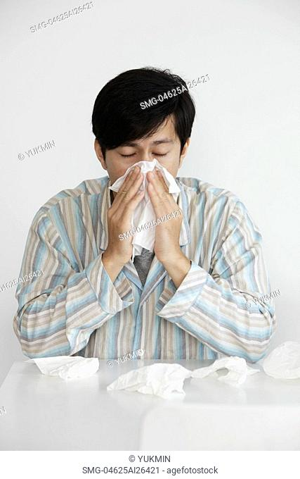 Young man blowing his nose, sneezing