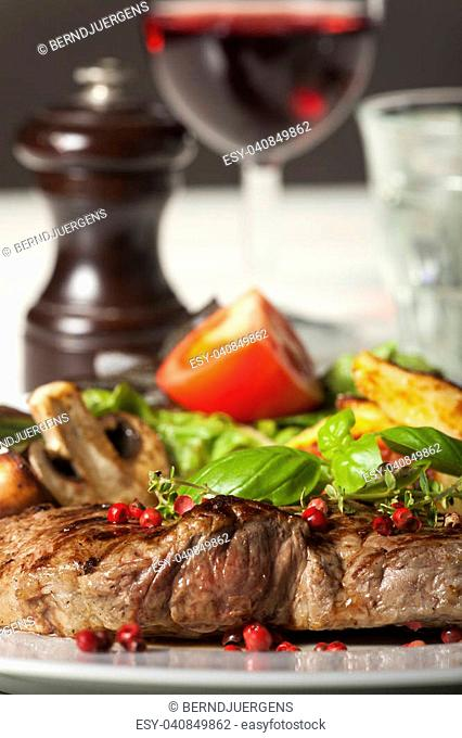 closeup of a beef steak with peppercorns