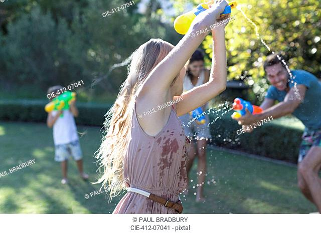 Family playing with water guns in backyard