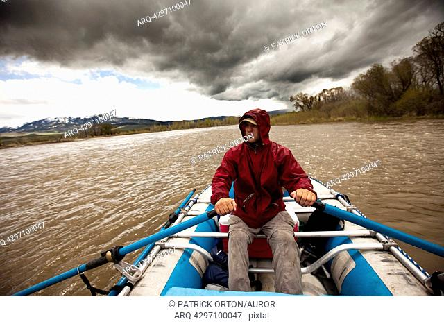 A man rafts down a rive under stormy skies in Montana