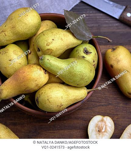 ripe green pears in a brown clay bowl on a table, close up