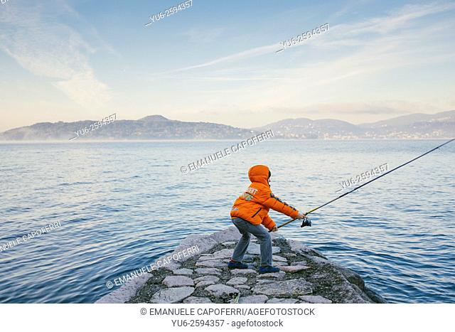 Child fishing on Lake Maggiore, Italy