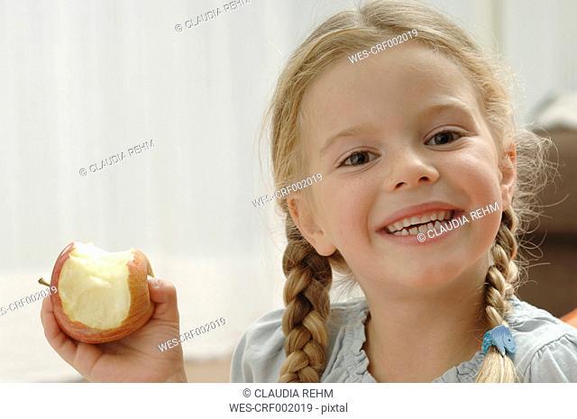 Germany, Bavaria, Girl holding apple, portrait, smiling