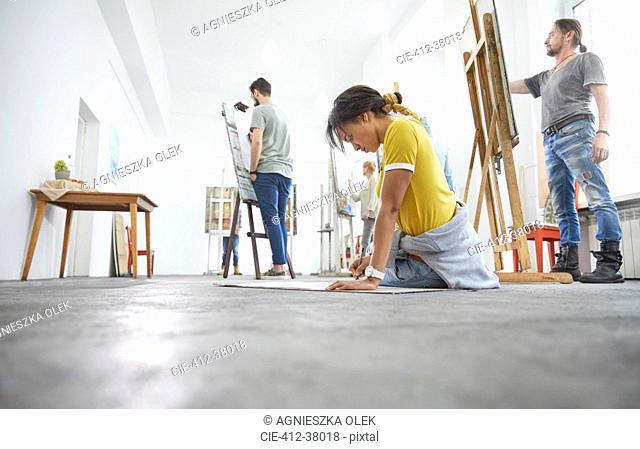 Female artist sketching on floor in art class studio