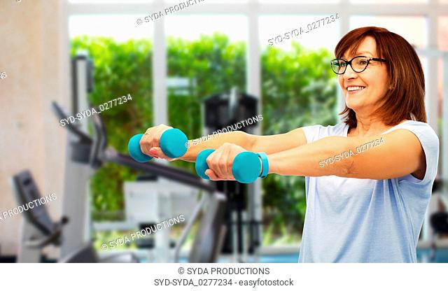happy old woman with dumbbells exercising in gym