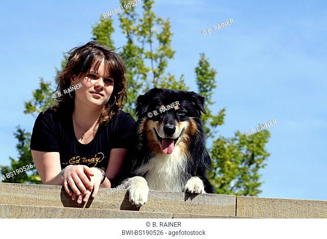 Australian Shepherd (Canis lupus f. familiaris), girl lys next to her dog on a stair