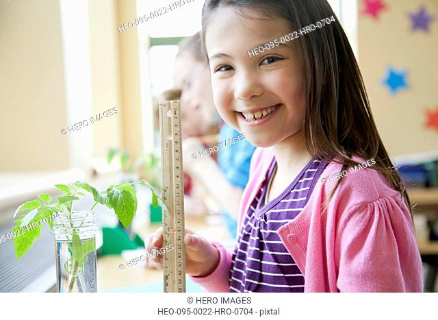 Smiling, elementary student measuring plant