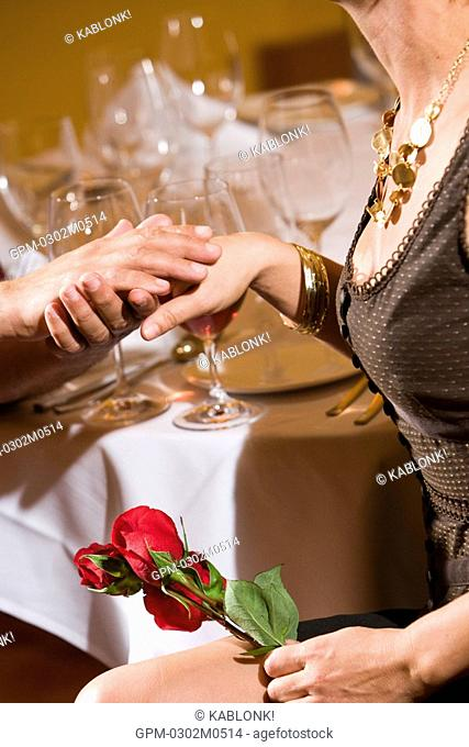 Couple holding hands at table in upscale restaurant, detail