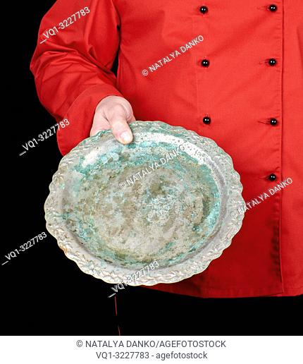 chef in red uniform holds in his hand an empty iron round dish, black background