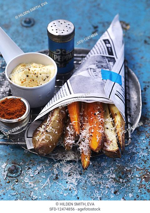 French fries and sweet potato fritters in a paper bag with parmesan and mayonnaise