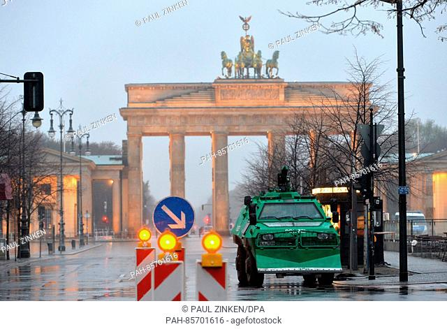 An armoured truck and police vehicles in front of Brandenburger Tor in preparation for the visit of US President Barack Obama in Berlin, Germany