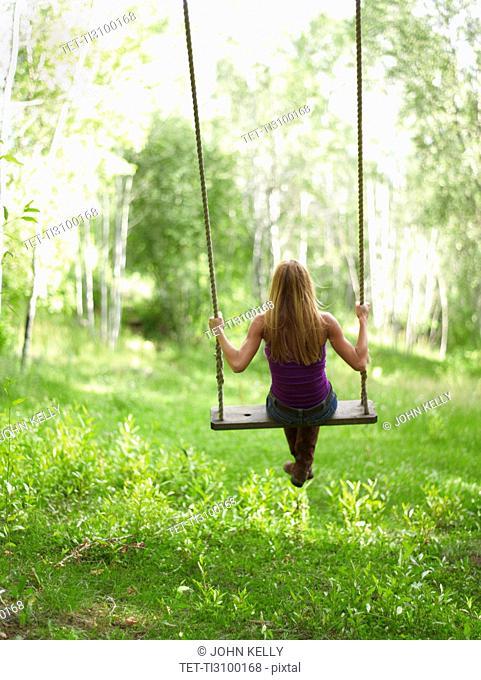 USA, Colorado, Mature woman swinging, rear view