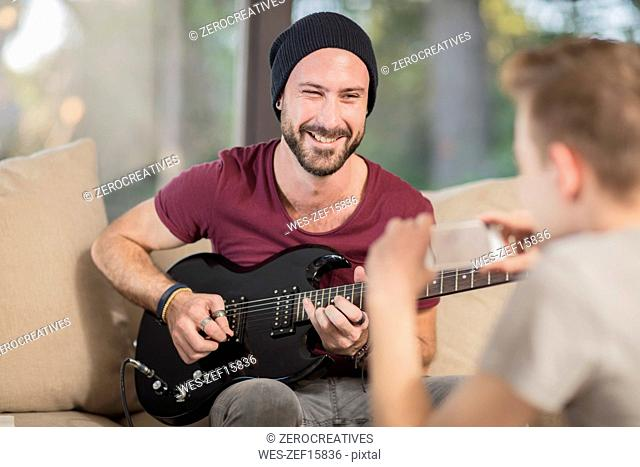 Young man at home sitting on couch playing guitar for teenage boy taking a cell phone picture
